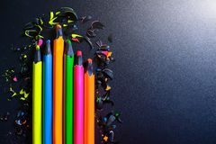 Bright colored pencils and shavings from the pencils on a dark background stock illustration