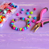 Bright colored bracelet made of plastic buttons. Handmade cute kids jewelry. Children's diy Royalty Free Stock Photography