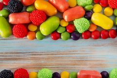 Bright colored candy on a blue wooden background with copyspace Stock Photo