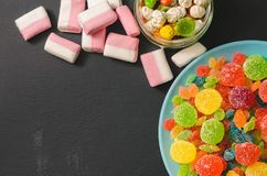 Bright colored candy, candy, marshmallow, sweets on a dark background on blue plate stock photography