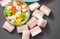 Bright colored candy, candy, marshmallow, sweets on a dark background on blue plate Royalty Free Stock Photos