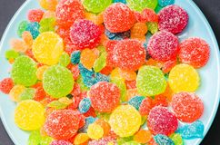 Bright colored candy, candy, marshmallow, sweets on a dark background on blue plate Royalty Free Stock Photography