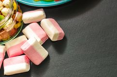 Bright colored candy, candy, marshmallow, sweets on a dark background on blue plate royalty free stock image