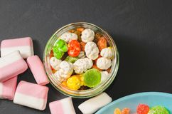 Bright colored candy, candy, marshmallow, sweets on a dark background on blue plate Royalty Free Stock Photo