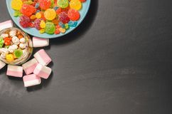 Bright colored candy, candy, marshmallow, sweets on a dark background on blue plate Stock Photos