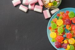 Bright colored candy, candy, marshmallow, sweets on a dark background on blue plate Stock Image