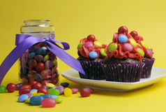Bright colored candy cupcakes with candy jar Stock Photo