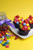 Bright colored candy cupcakes with candy jar - vertical. Royalty Free Stock Images