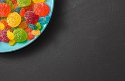 Bright colored candy, marmalade, sweets in a blue plate on a dark background stock photos