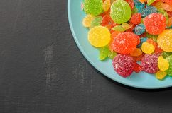 Bright colored candy, marmalade, sweets in a blue plate on a dark background Royalty Free Stock Images