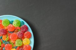 Bright colored candy, marmalade, sweets in a blue plate on a dark background Royalty Free Stock Photos