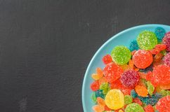 Bright colored candy, marmalade, sweets in a blue plate on a dark background Stock Photo