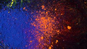 Bright colored dust explosion on a black background, art concept. Motion of blue and orange powder inks, multicolored stock image