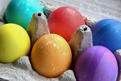 Bright colored Easter eggs in an egg carton Stock Photo