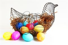 Bright colored Easter eggs in a wire chicken basket. Bright colored Easter eggs in a wire chicken basket,  on a white background Stock Photography