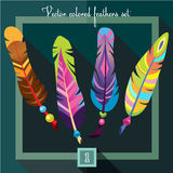 Bright colored feathers with beads on a emerald green background. Stock Photos