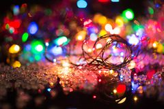 Bright colored garlands bulb shines in the dark background, selective focus Royalty Free Stock Photography