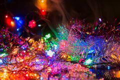 Bright colored garlands bulb shines in the dark background, selective focus Royalty Free Stock Photo