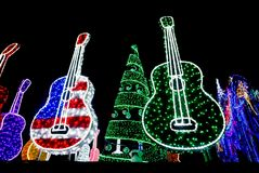 Bright Colored Guitars with Green Holiday Tree with Ornaments li. Bright Red, Red White and Blue and Purple and Green Guitars and Holiday Tree with Ornaments lit royalty free stock photos