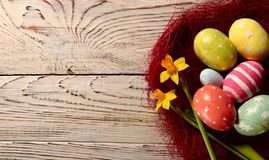 Happy Easter.Bright colored painted eggs on the right in a red nest of grass on a brown wooden surface. Bright colored painted eggs on the right in a red nest royalty free stock photo