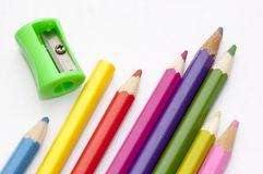 Bright colored pencils and a sharpener. Color pencils and a sharpener on a white sheet of paper Royalty Free Stock Images