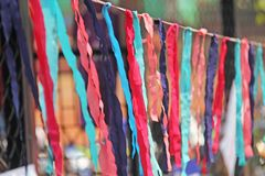 Bright colored ribbons hang and flutter in the wind. Fair holiday festival decoration. India, Goa, Arambol.  royalty free stock photography