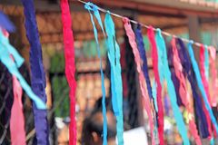 Bright colored ribbons hang and flutter in the wind. Fair holiday festival decoration. India, Goa, Arambol.  stock photos