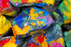 Bright colored stones with paint. Abstract Background Bright Colored Stones With Paint, Bizarre to Spread Paint on the Surface Royalty Free Stock Photography