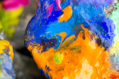 Bright colored stones with paint. Abstract Background Bright Colored Stones With Paint, Bizarre to Spread Paint on the Surface Royalty Free Stock Photos