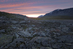Bright colored striped sunset over the harsh rocky Sarek landscape Stock Image