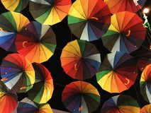 Bright colored umbrellas, painted in all the primary colors of the palette, against the background of the dark night sky. Close up stock photography