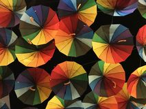 Bright colored umbrellas, painted in all the primary colors of the palette, against the background of the dark night sky. Close up royalty free illustration