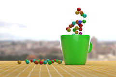 Bright colorful balls on yellow tile and in green mug Stock Photos