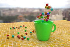 Bright colorful balls on yellow tile and in green mug Royalty Free Stock Photo