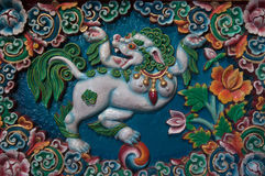 Bright colorful bas-relief with an image of the mythical figure of snow lion, a symbol of Tibetan Buddhism, surrounded by rich orn Stock Images