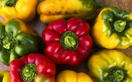 Bright, colorful, beautiful, ripe peppers on a wooden background. Royalty Free Stock Image
