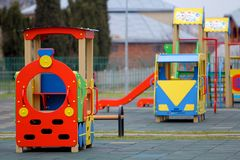 Bright colorful big toy cars on nursery playground with soft rubber flooring on bright sunny summer day. Perfect place for. Children activities and recreation royalty free stock image