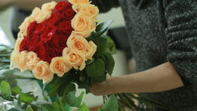 Bright colorful bouquet of red and peach roses, florist woman gathers a bouquet stock video footage