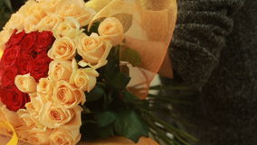 Bright colorful bouquet of red and peach roses, florist woman gathers a bouquet stock video