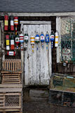 Bright, colorful bouys hanging on a rustic shed Stock Image