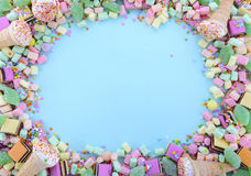 Bright colorful candy on pale blue wood table. Royalty Free Stock Images
