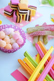 Bright Colorful Candy on Pale Bluw Wood Table. Royalty Free Stock Images