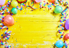 Bright colorful carnival or party frame on yellow. Bright colorful carnival or party frame of balloons, streamers and confetti on a rustic yellow wood table with stock photo