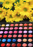 Bright colorful cosmetics. Display of bright, colorful make up with flowers, for natural cosmetics concept Royalty Free Stock Photos