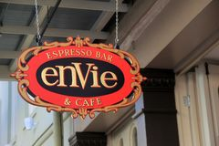 Bright and colorful sign welcoming visitors into Envie Espresso Bar & Cafe, New Orleans, 2016. Bright and colorful detail in gaily painted hanging sign that royalty free stock image