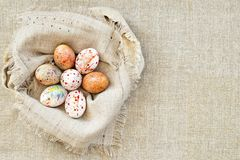 Bright colorful easter eggs in a nest of canvas fabric stock image