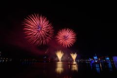 Beautiful colorful fireworks display on the urban lake for celebration on dark night background. Bright and colorful fireworks against a black night sky Stock Photo