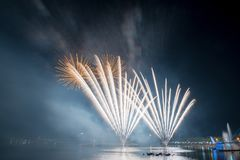 Beautiful colorful fireworks display on the urban lake for celebration on dark night background royalty free stock photography