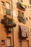 Bright and Colorful Italian balconies. Colorfully orange. covered balconies and plants balanced on window sills Stock Photography