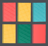 Bright colorful lined and squared notebook paper are stuck on dark background.  Stock Photos